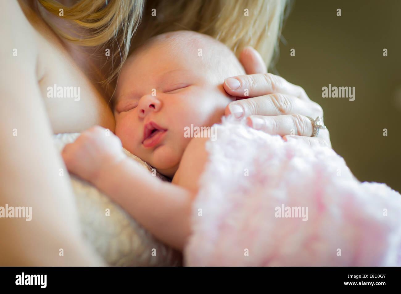 Sanfte Hände der Mutter hält ihr kostbares neugeborenes Baby Girl. Stockbild