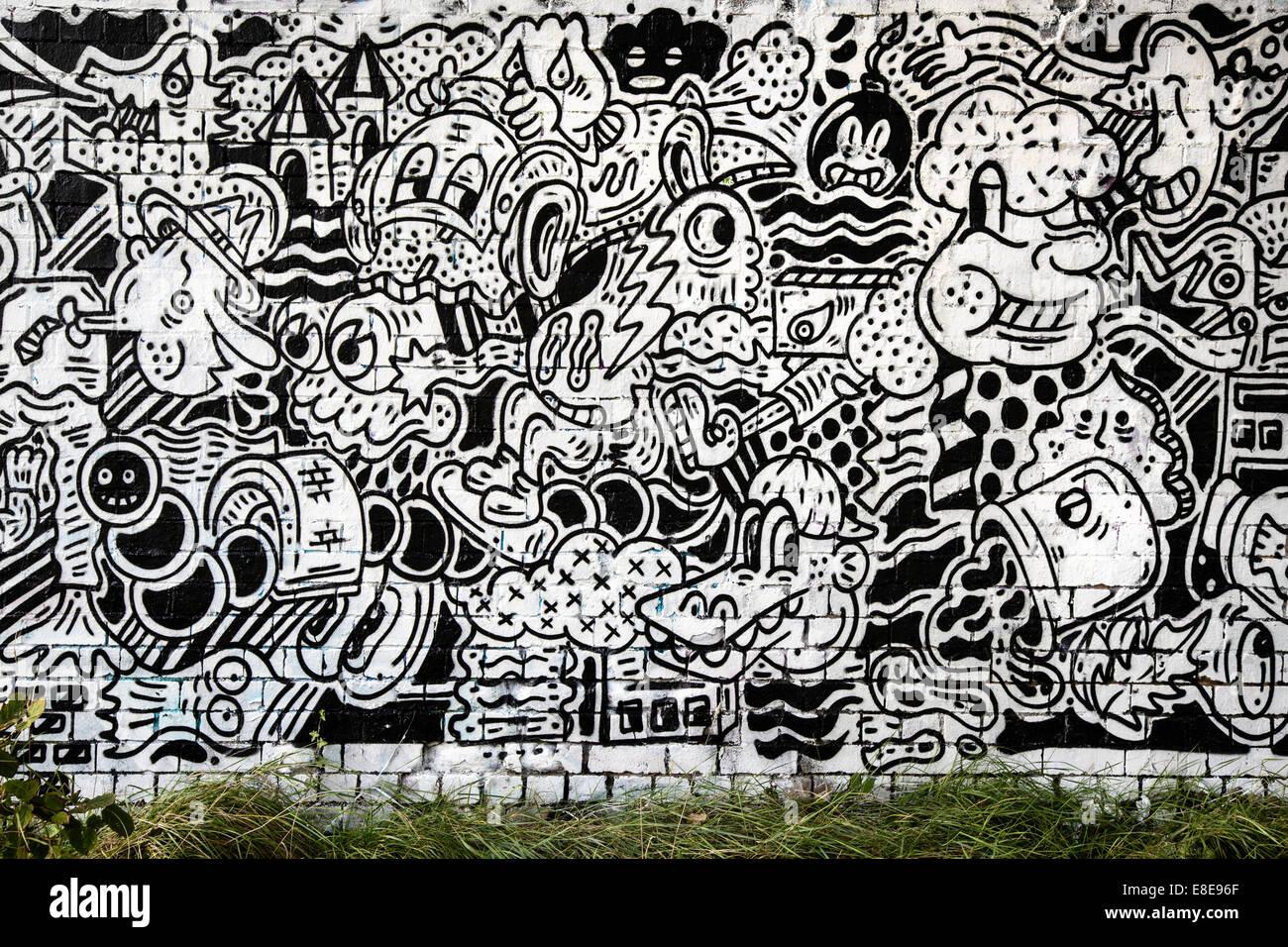 Riesige schwarze und weiße Comic-Buch Graffiti Wandmalerei unter einer Eisenbahnbrücke in Bristol Stockfoto