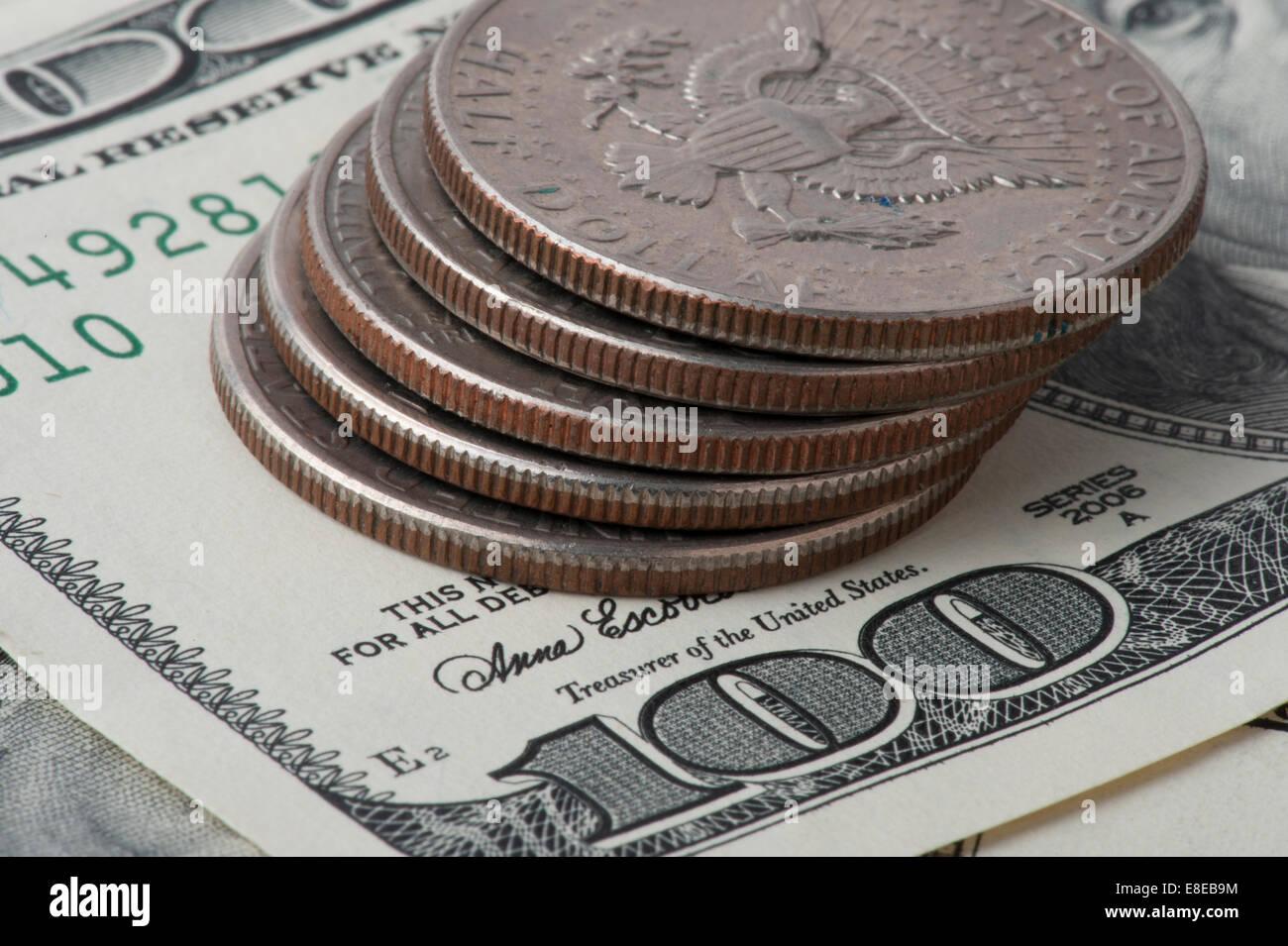 fünf halbe Dollar-Münzen gestapelt auf $100-Dollar-Scheine Stockbild