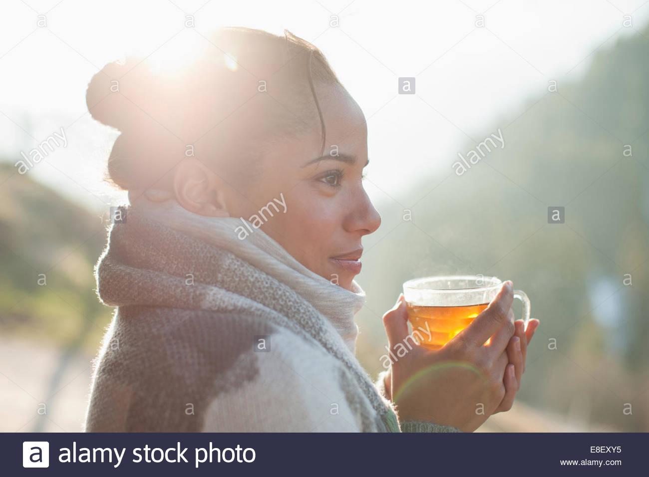 Nahaufnahme eines lächelnden Frau trinkt Tee im freien Stockbild