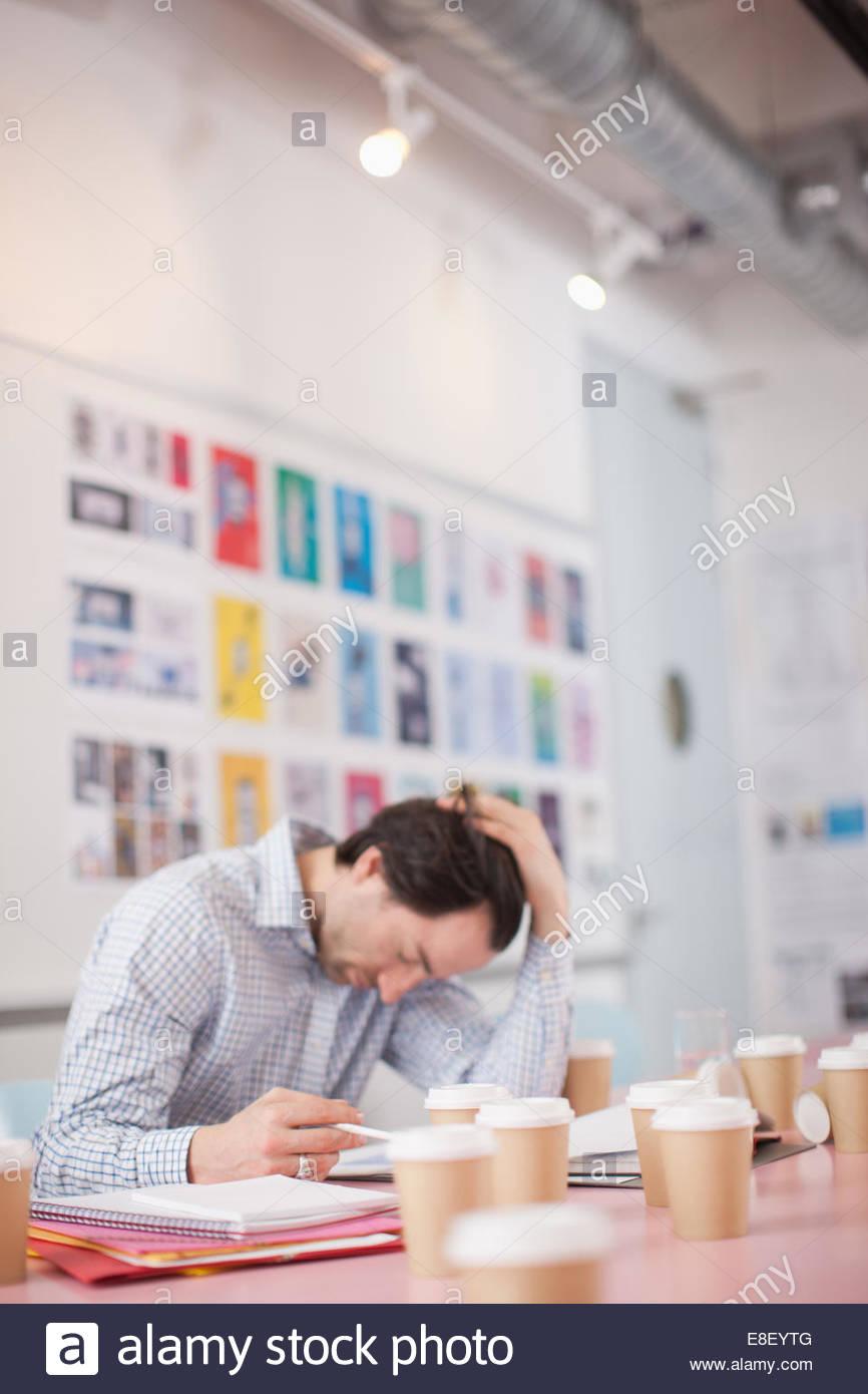 Geschäftsmann mit Kopf in Händen, umgeben von Kaffeetassen im Büro Stockbild