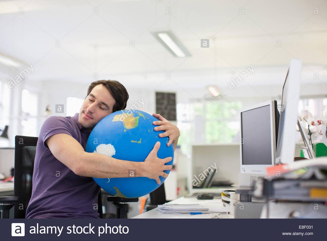 Geschäftsmann mit Augen geschlossen umarmt Globus am Schreibtisch im Büro Stockbild