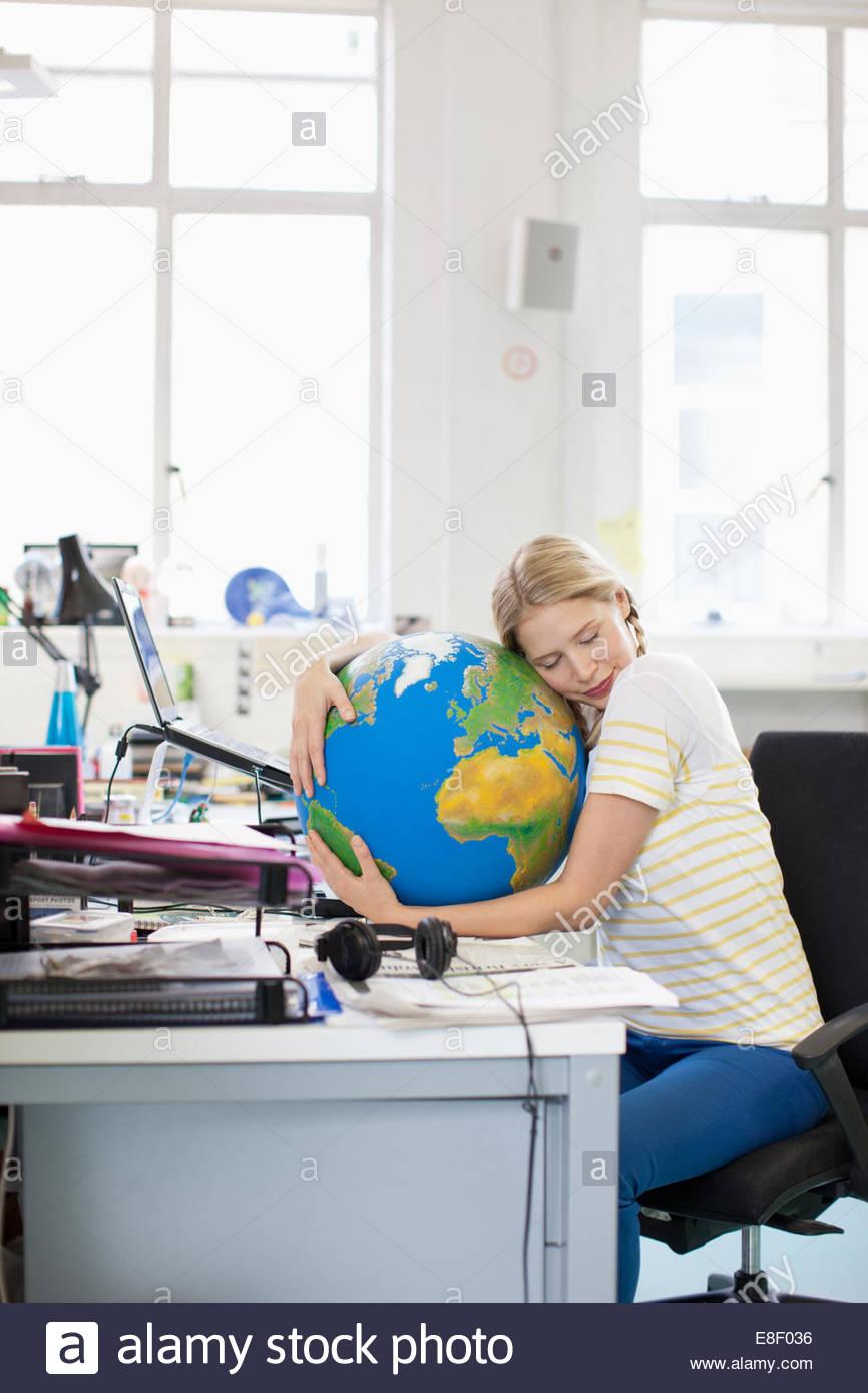 Geschäftsfrau mit Augen geschlossen umarmt Globus am Schreibtisch im Büro Stockbild