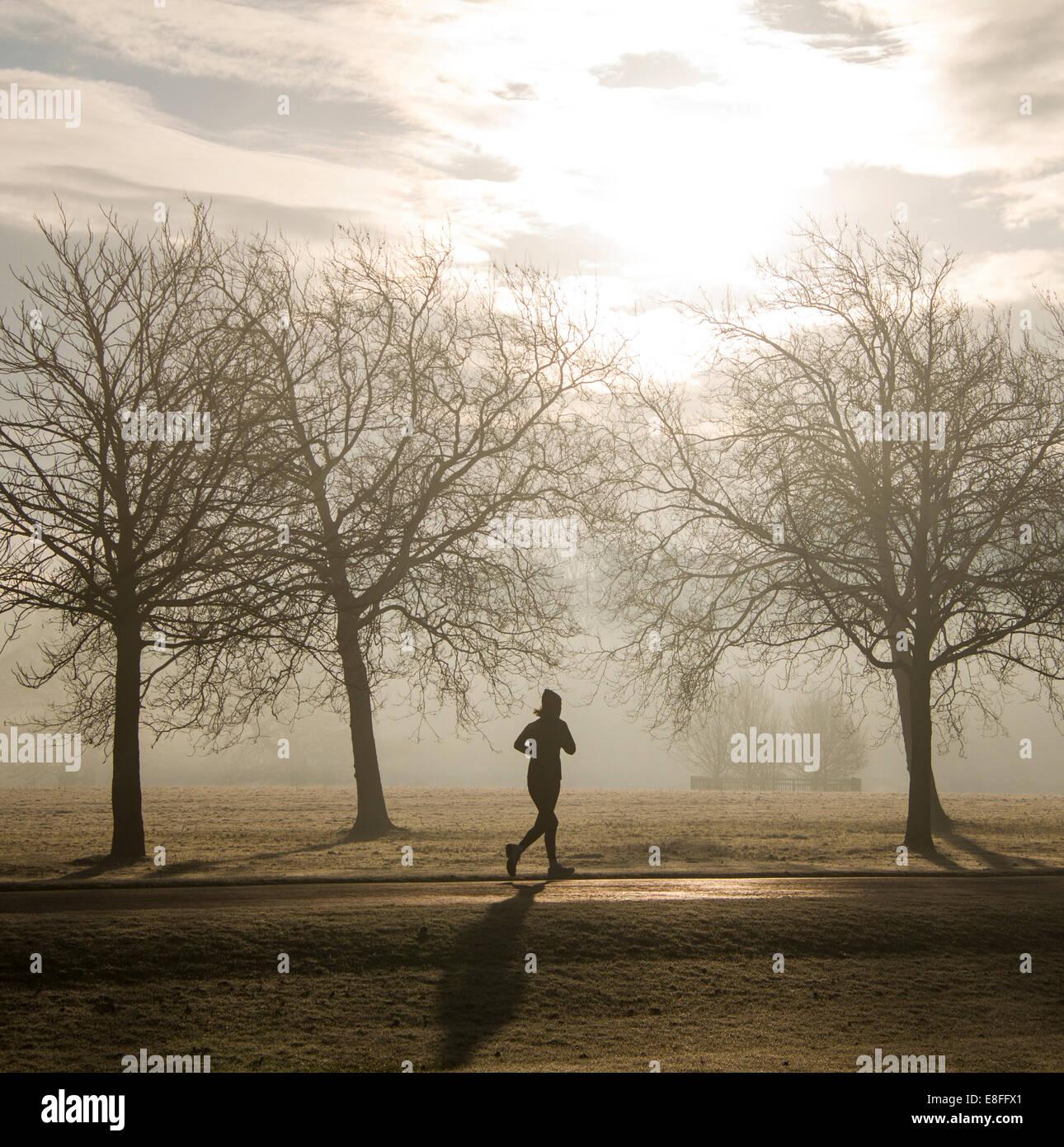 Silhouette einer Frau läuft durch den Park, England, UK Stockbild