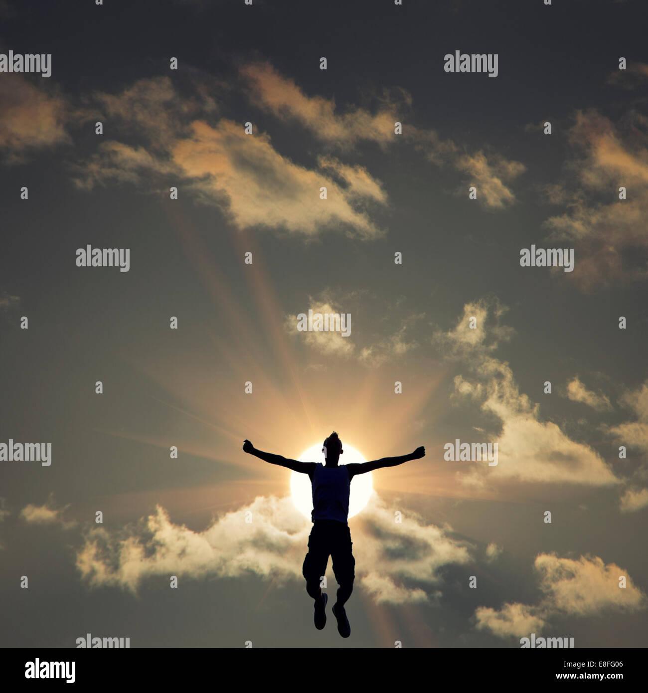 Silhouette der Mann springt vor der Sonne Stockbild