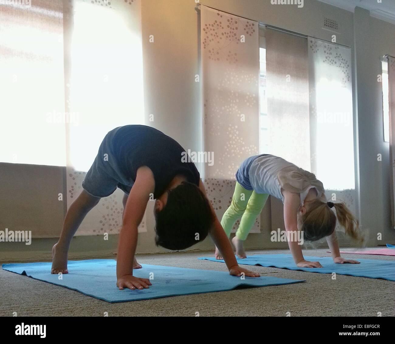 Zwei Kinder machen unten Hund Yoga darstellen Stockbild