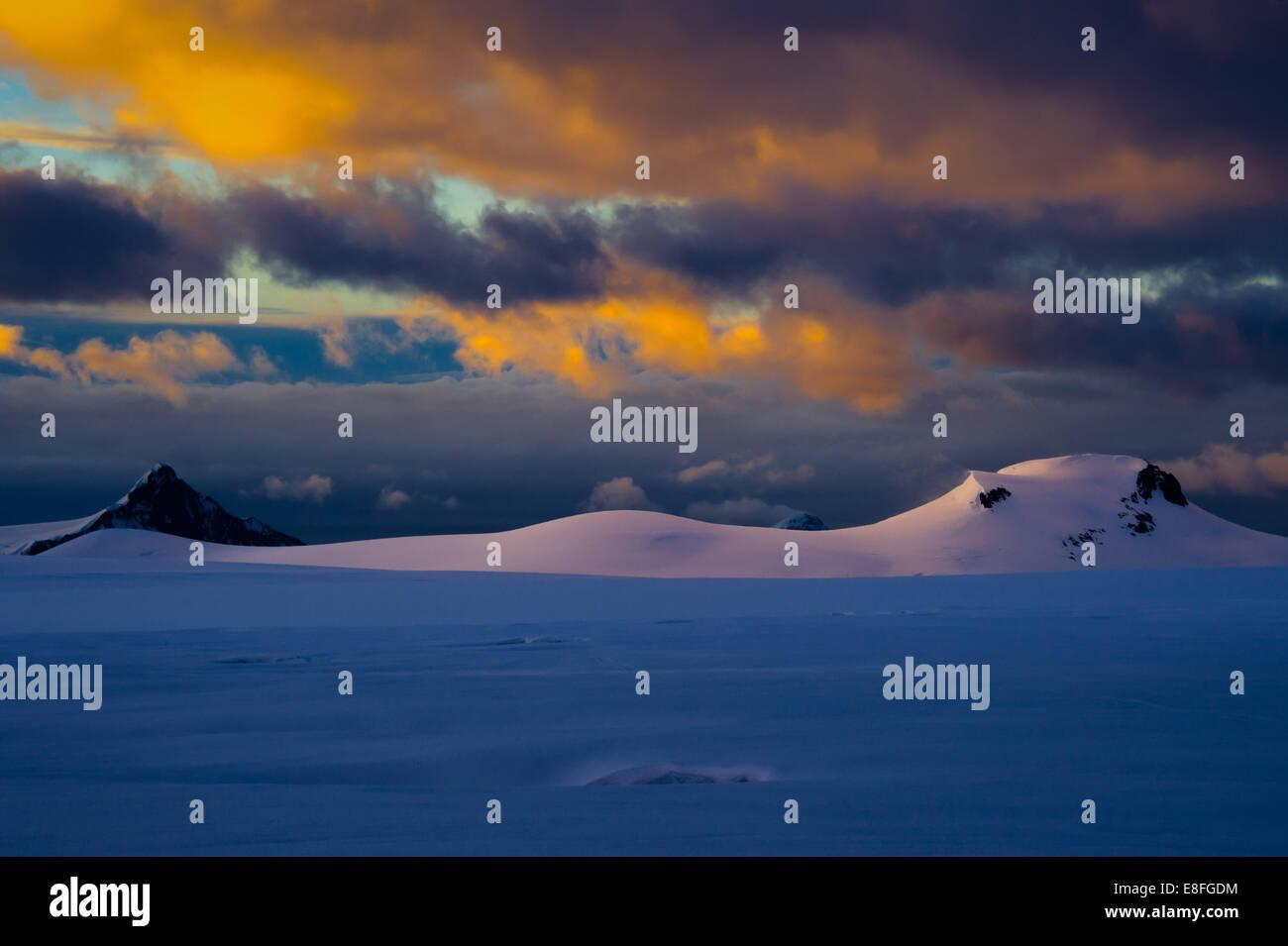 Wolken über schneebedeckte Berge Stockbild