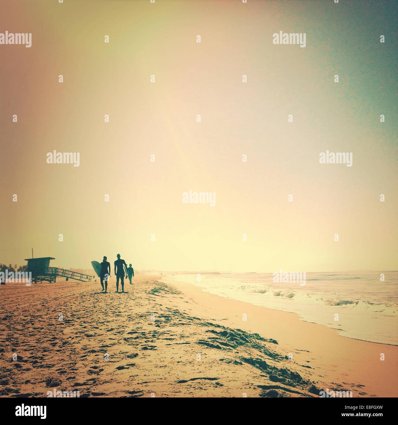 Silhouette der Surfer Strand entlang spazieren Stockfoto