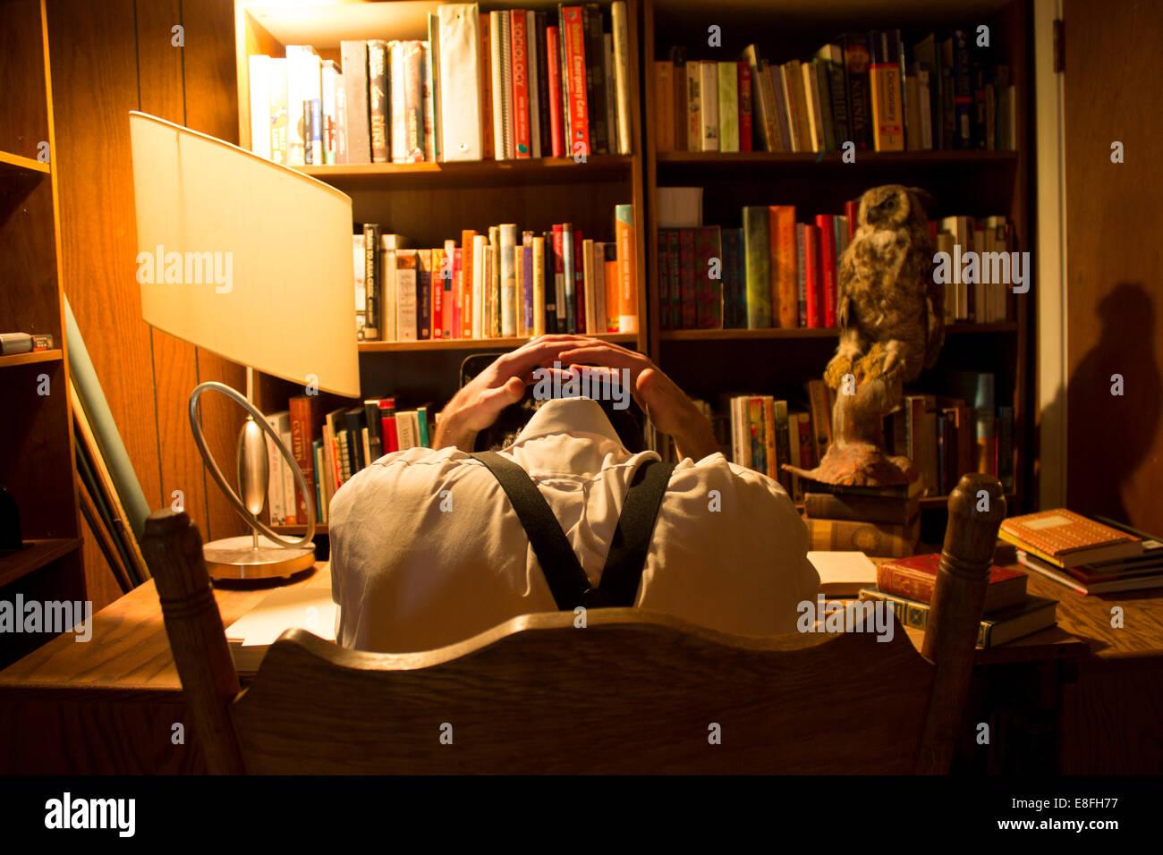 Mann, sitzend am Schreibtisch mit Schreibblockade Stockbild
