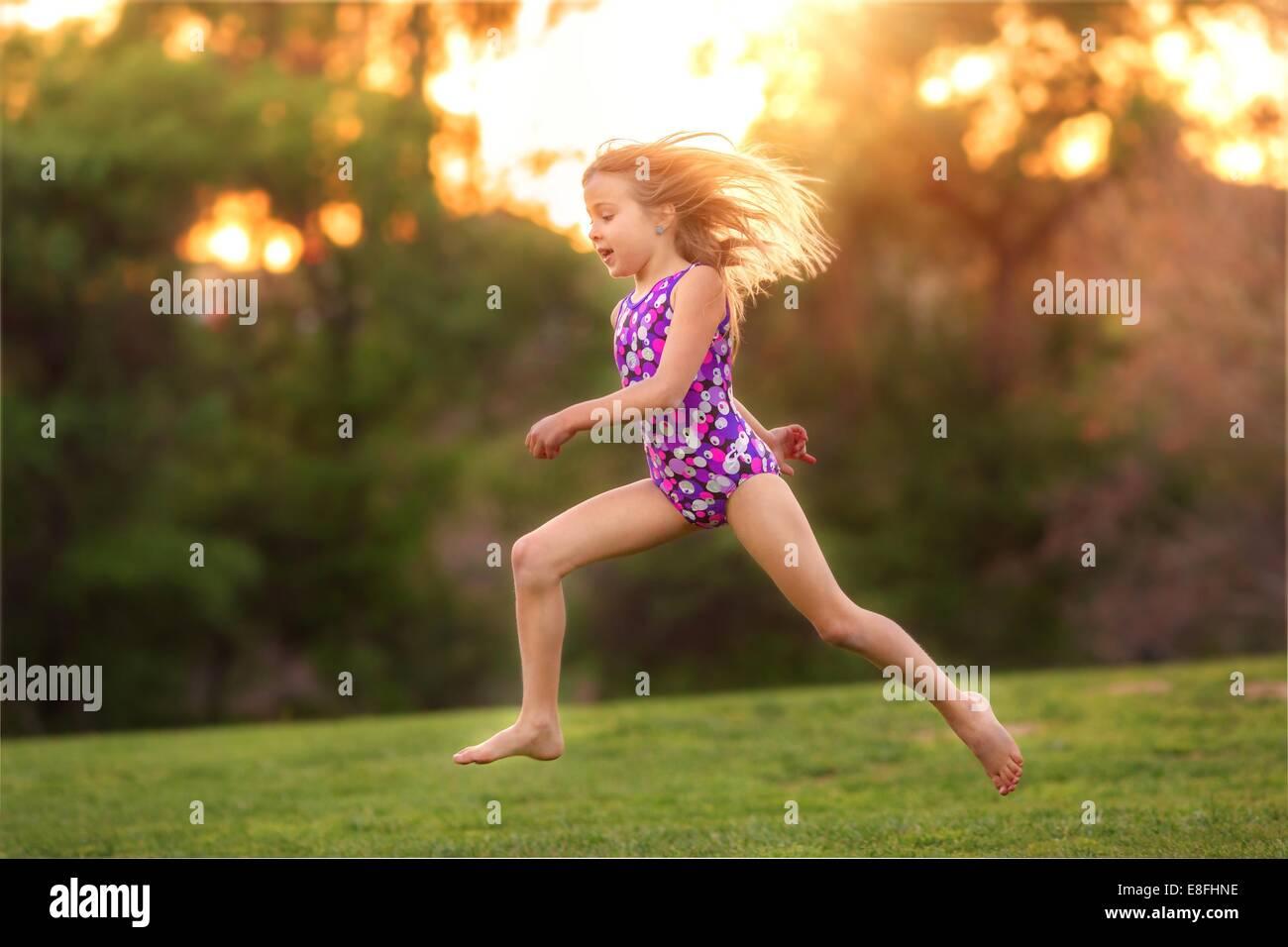 USA, kleines Mädchen (8-9) tragen Badeanzug springen auf der Rückseite yard Stockbild