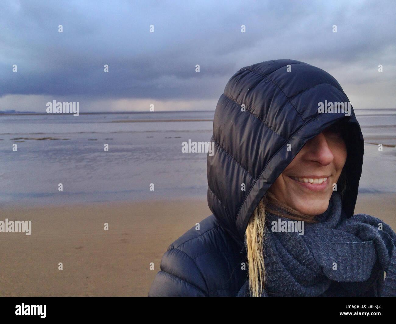 Somerset, UK lächelnde Frau am Strand bei stürmischem Wetter Stockbild