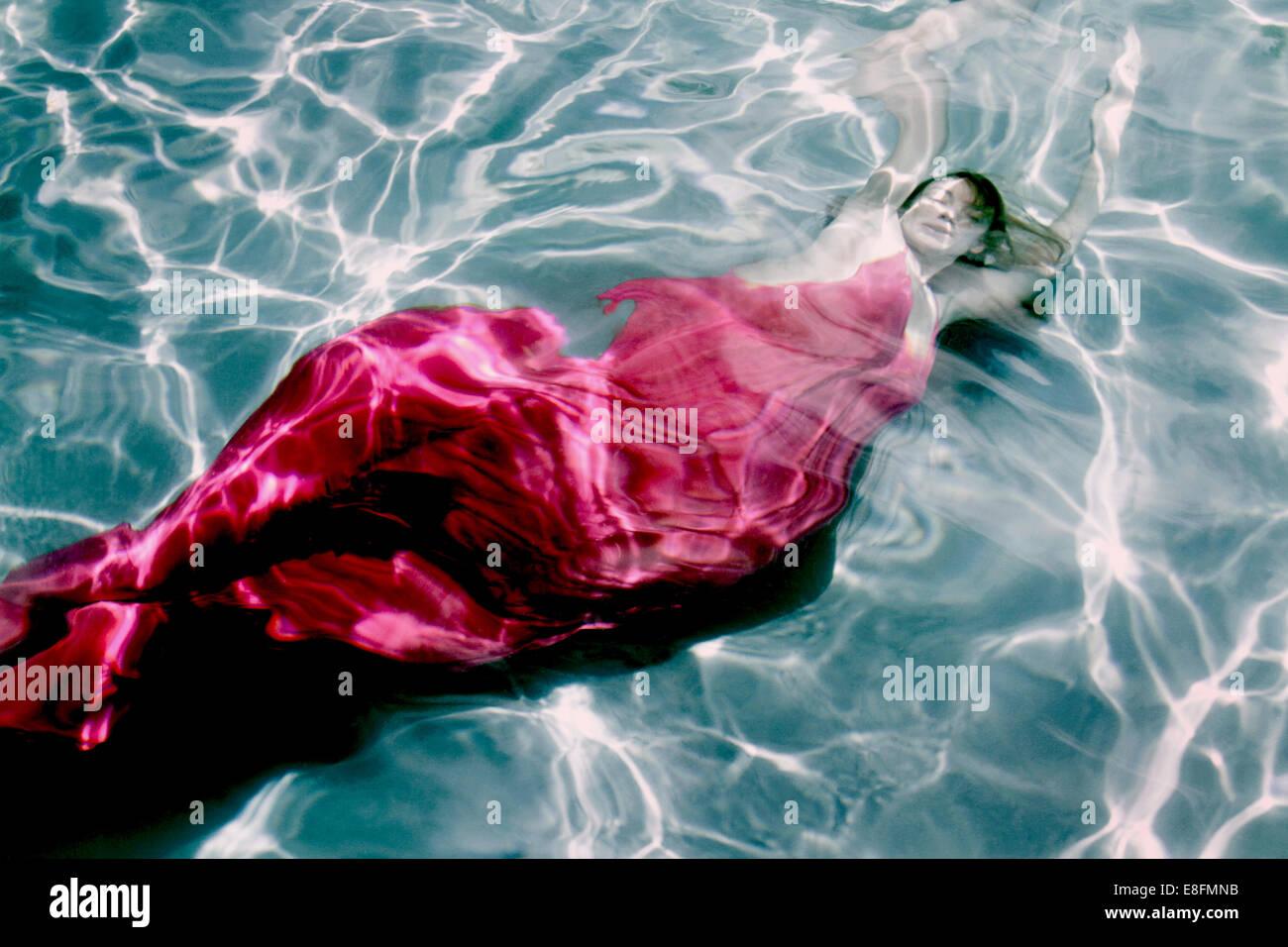 Frau im Kleid unter Wasser Stockbild