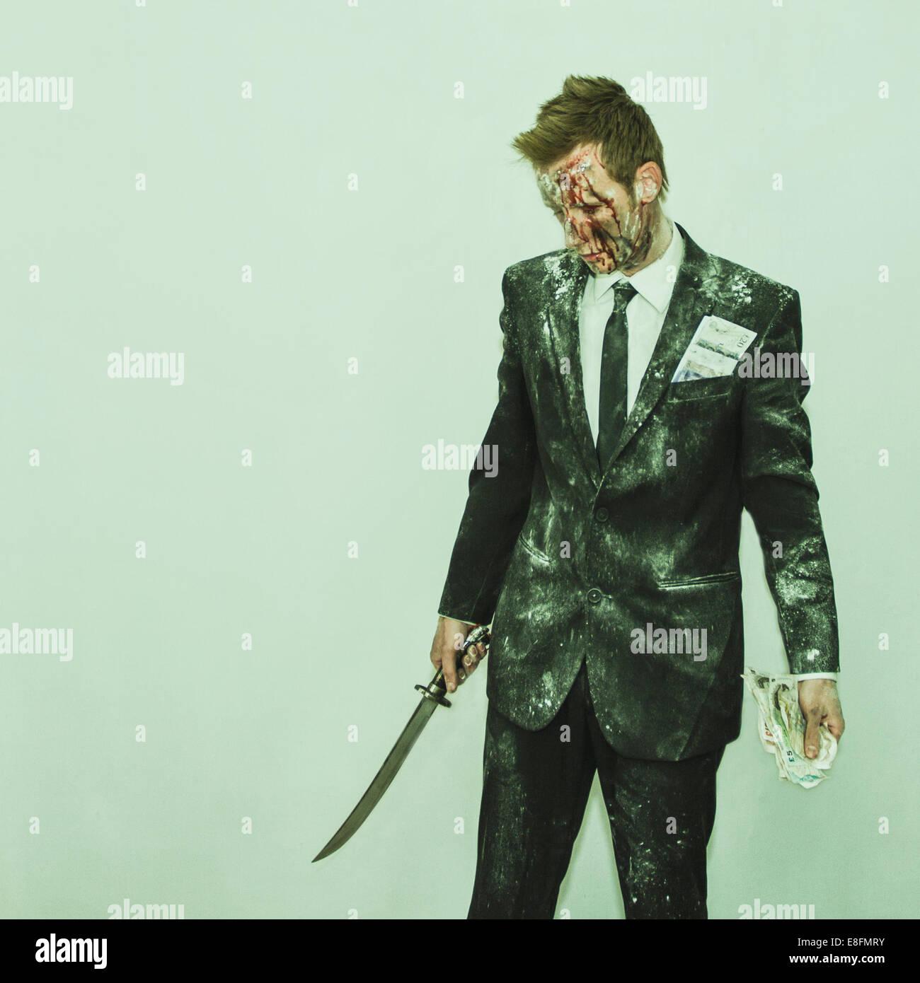 Mann im Anzug durchlöchern Schwert und Geld Stockbild