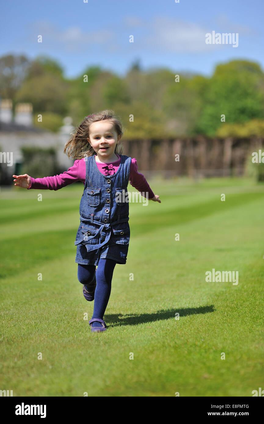 Kleines Mädchen (4-5) läuft auf dem grünen Rasen Stockbild