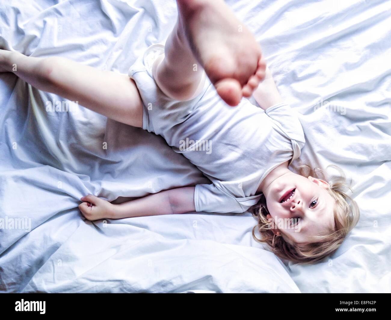 Junge auf Bett treten sein Bein in der Luft Stockbild