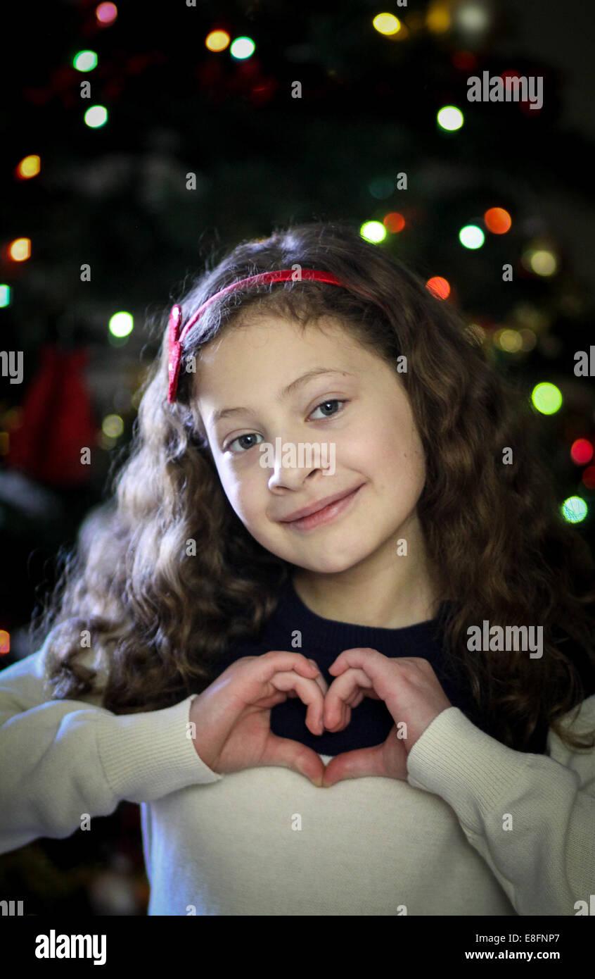 Mädchen, Herzform mit Händen vor der Weihnachtsbaum Stockbild