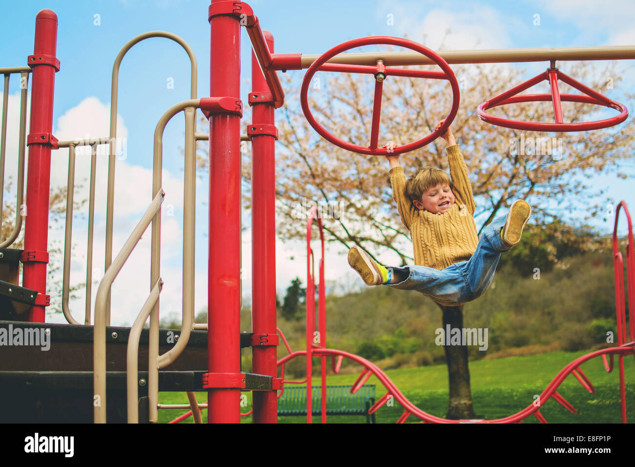 Fröhlicher Junge, der an einem Klettergerüst in einem Garten hängt Stockfoto