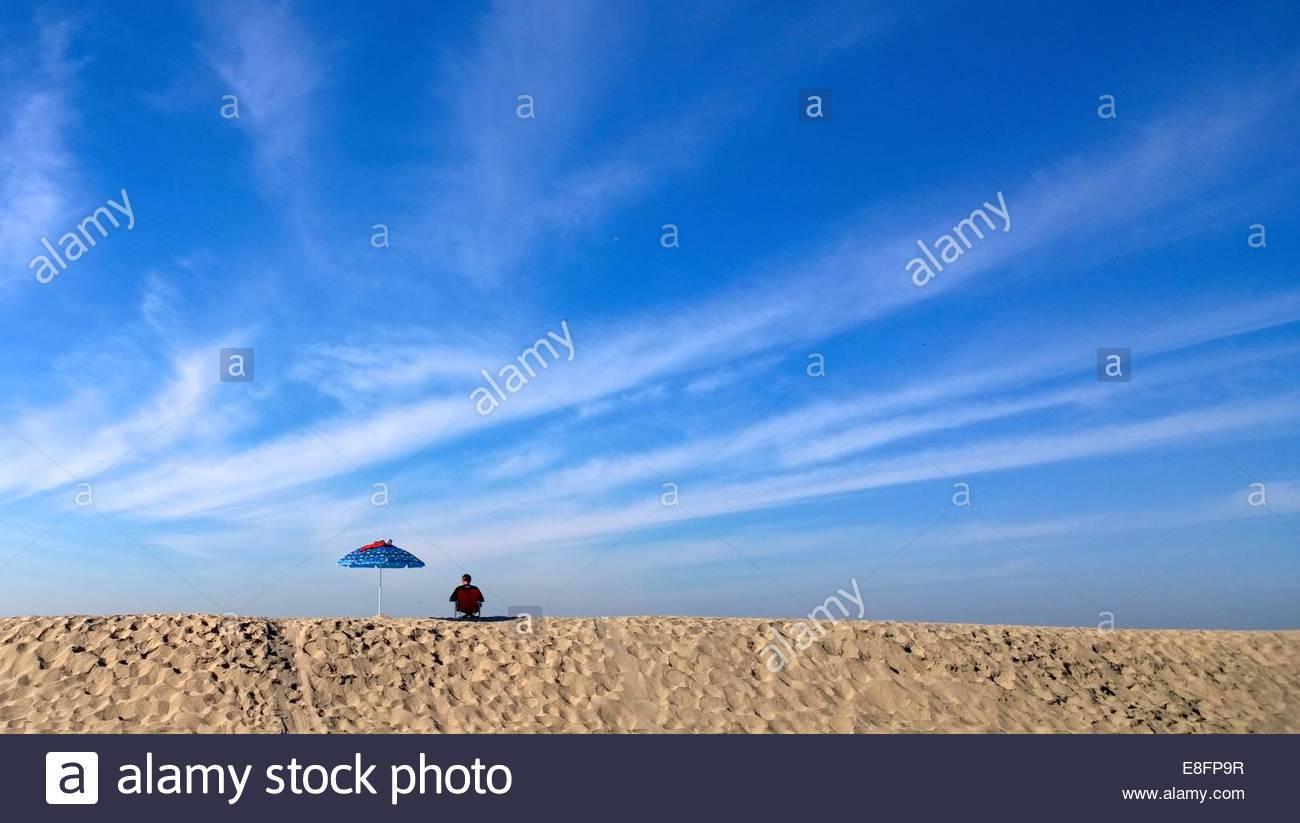 Rückansicht der Mann saß am Strand mit Sonnenschirm Stockbild