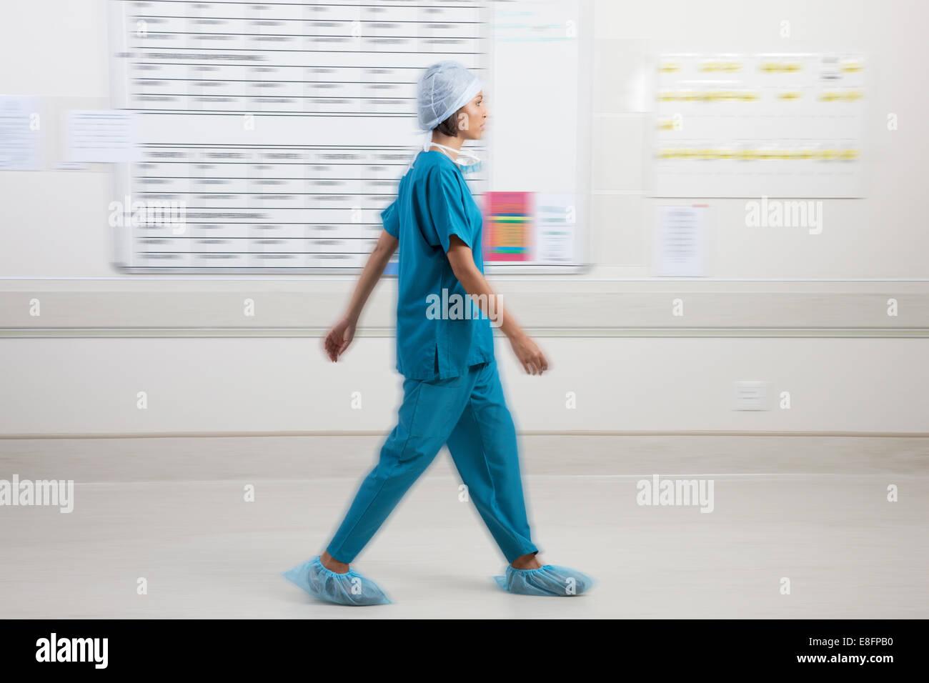 Chirurg, vorbei an Zeitplan Board im Krankenhaus Stockbild