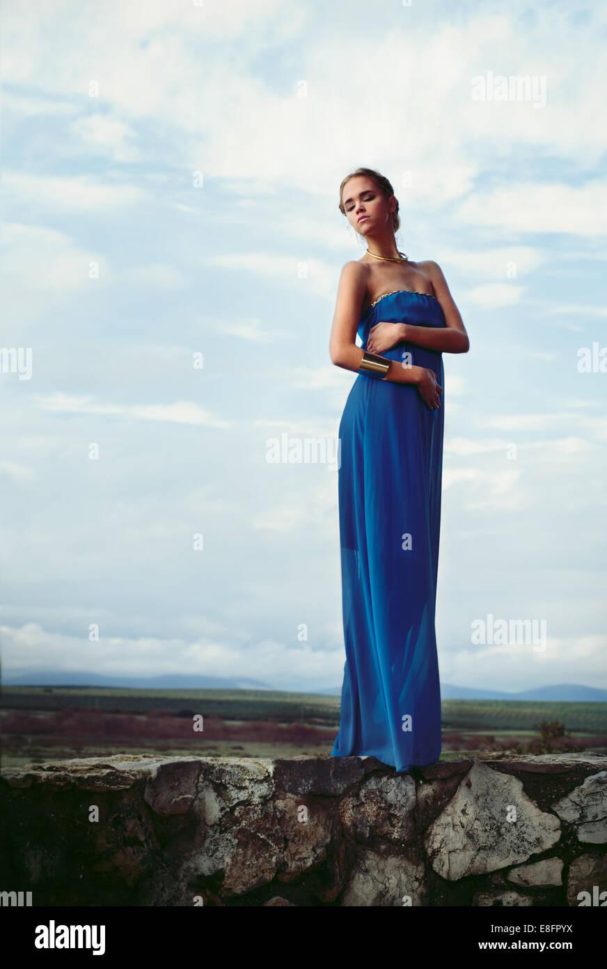 info for 1e7f7 e2413 Frau trägt blaue langes Kleid stehend auf Steinmauer ...