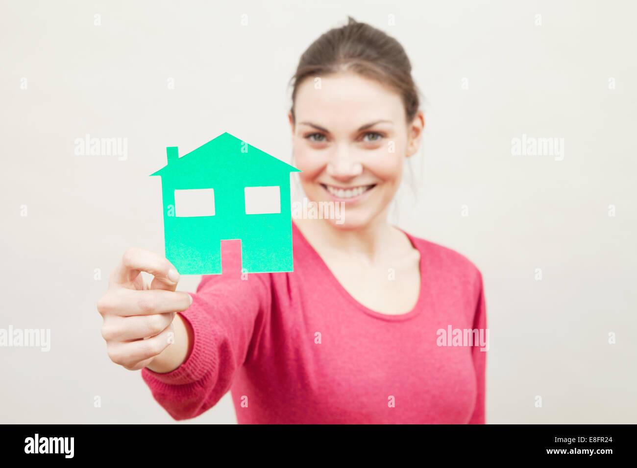 Junge Frau mit Papier Schneiden Sie aus einem Haus Stockbild