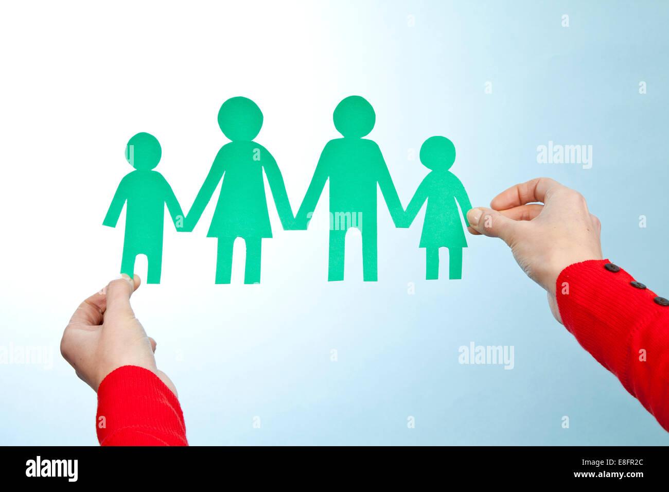 Hände halten Papier ausgeschnitten aus Familie Stockbild