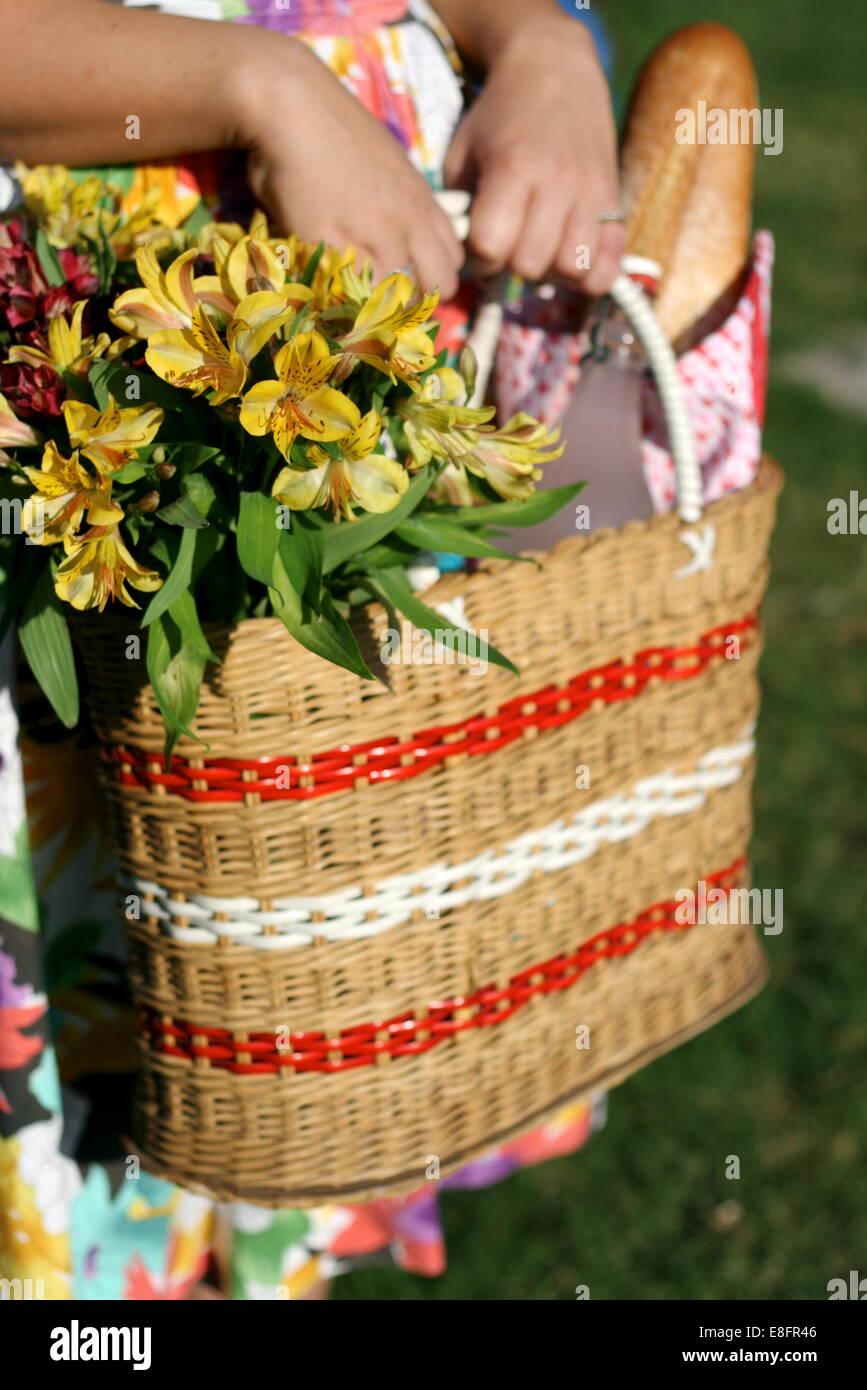 Picknick-Korb mit Blumen statt von Frau im geblümten Kleid Stockbild