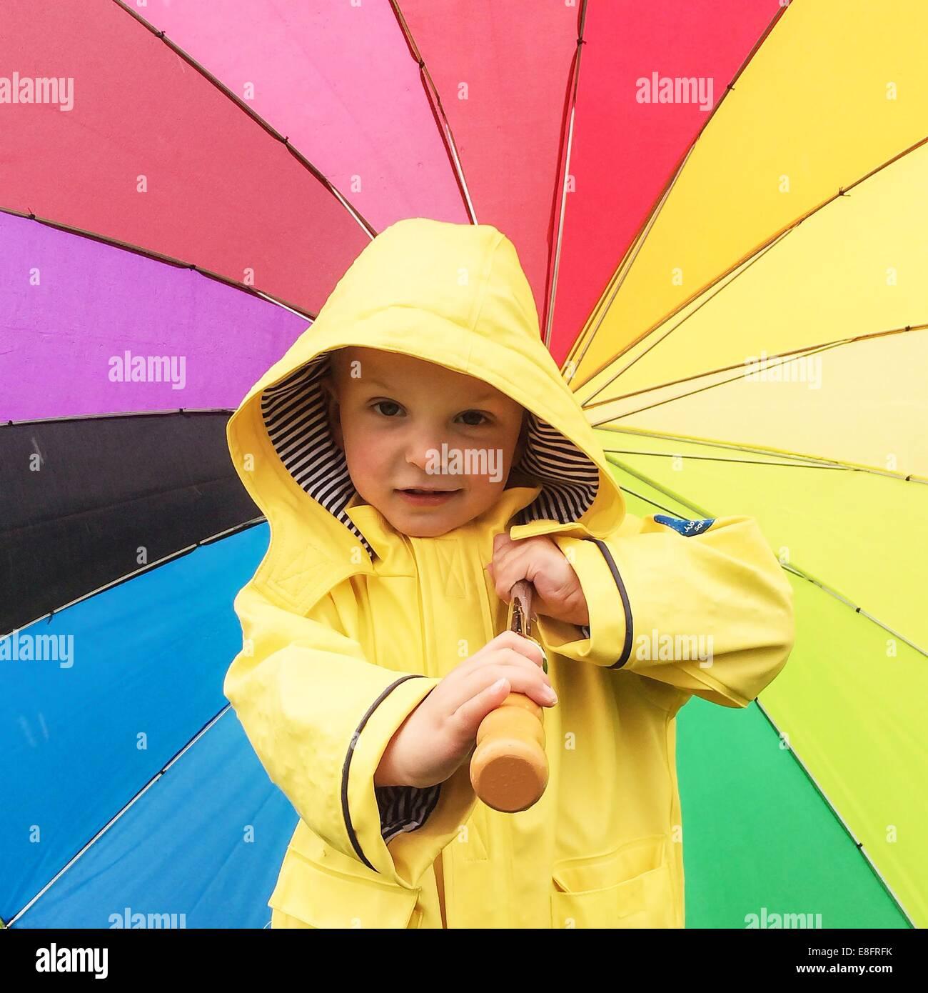 Junge in einem Regenmantel hält einen bunten Regenschirm Stockbild