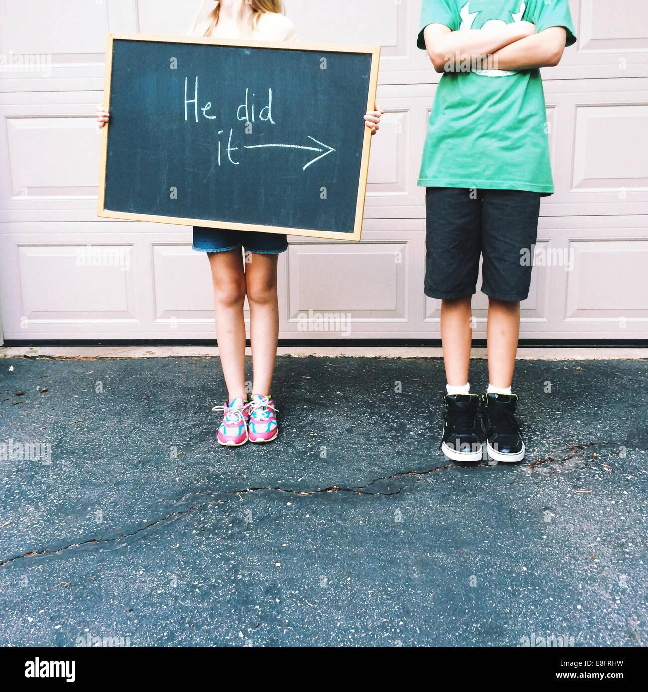 Junge steht neben einem Mädchen, das eine Tafel hält und sagt, er habe es getan Stockfoto