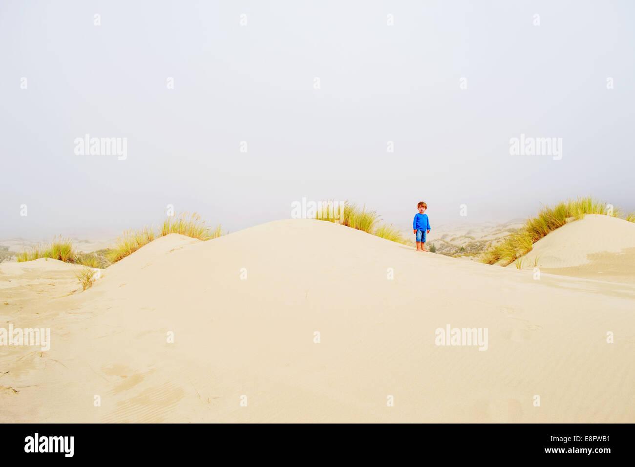 Junge (2-3) Stand auf der Sanddüne Stockbild