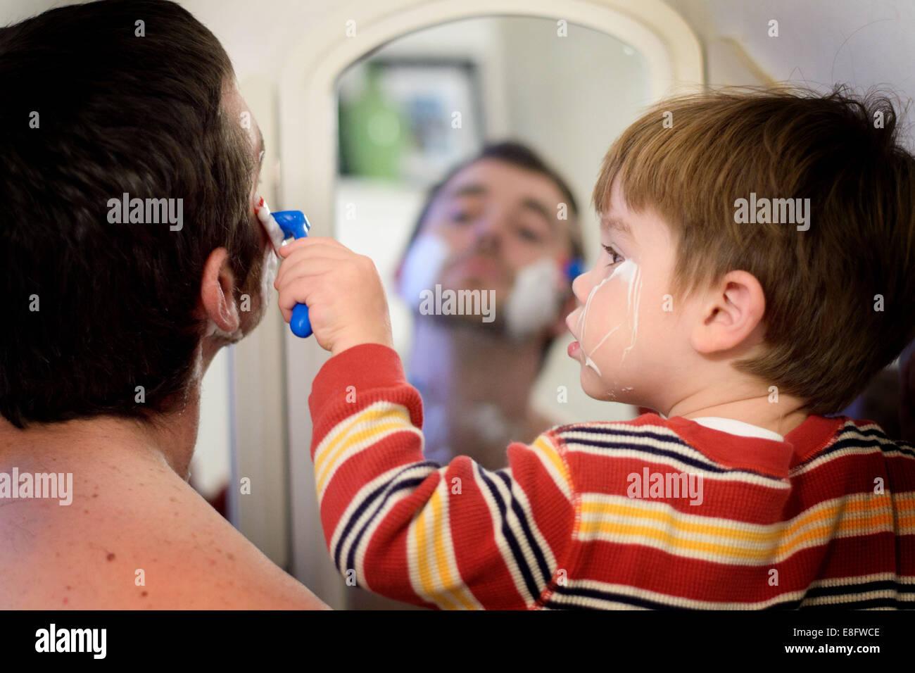 Junge hilft seinem Vater rasieren Stockfoto