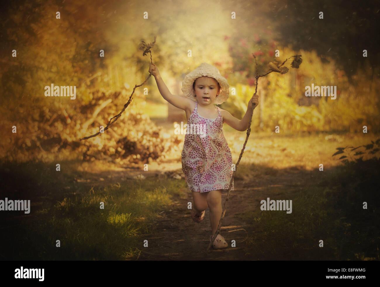 Mädchen mit trockenen Zweigen laufen Stockbild