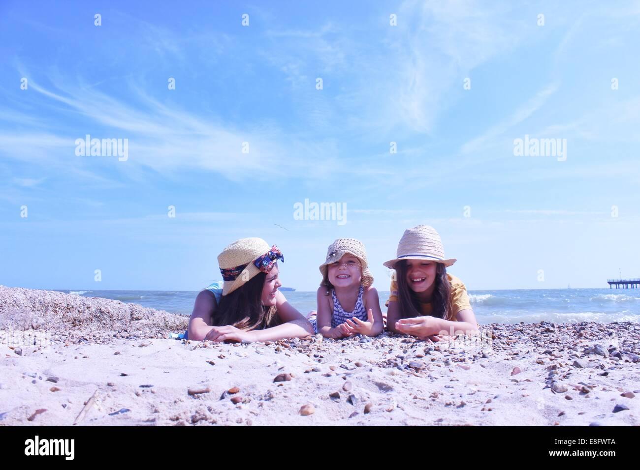 Drei Mädchen am Strand liegen an ihrer Vorderseite Stockbild