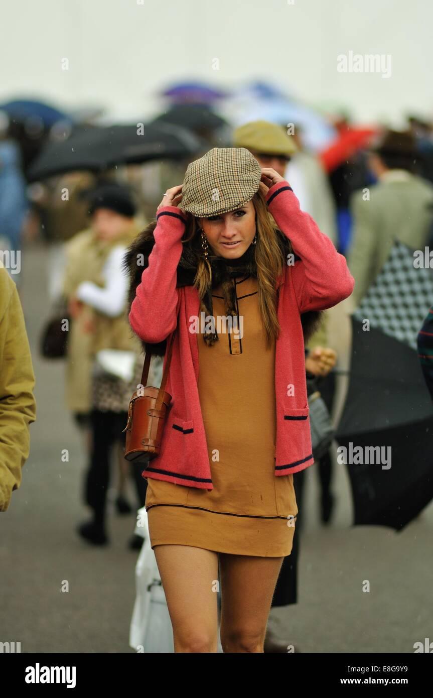 Eine junge Frau in einem 60er Jahre Outfit mit Tweed Tuch Kappe beim Goodwood Revival Stockbild