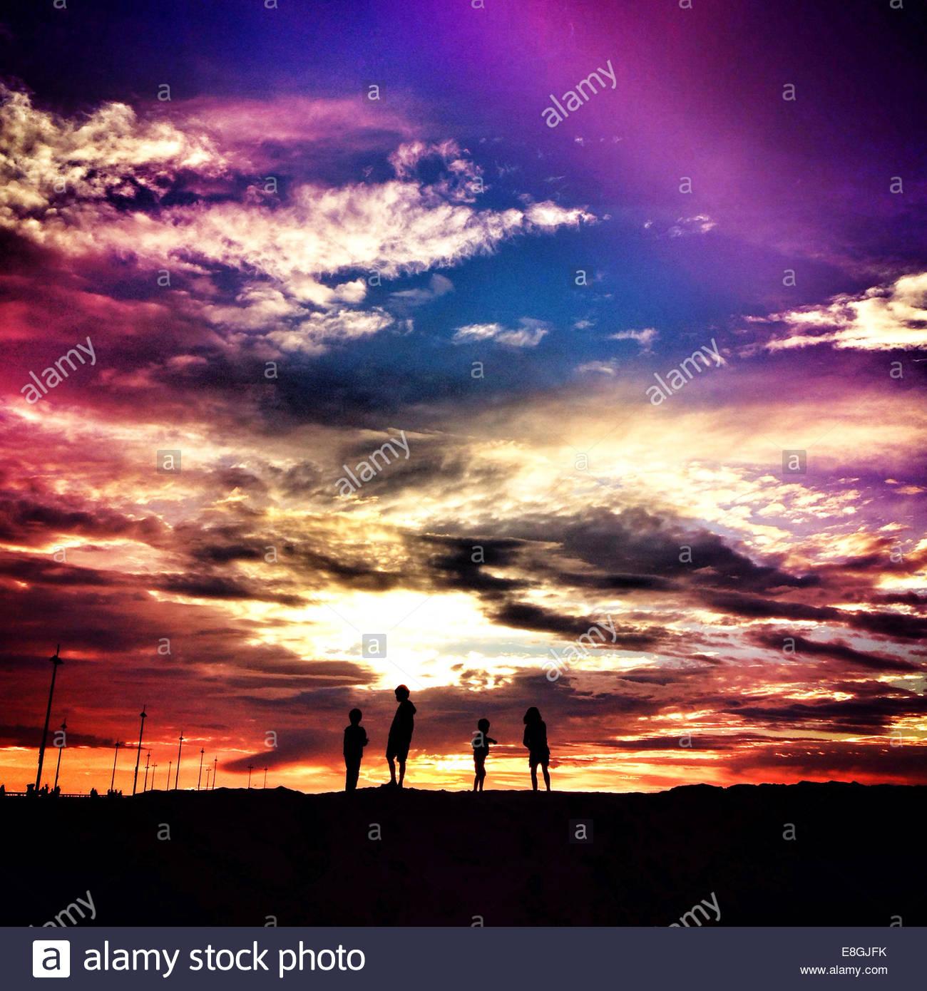 Silhouette von vier Kindern bei Sonnenuntergang Stockbild