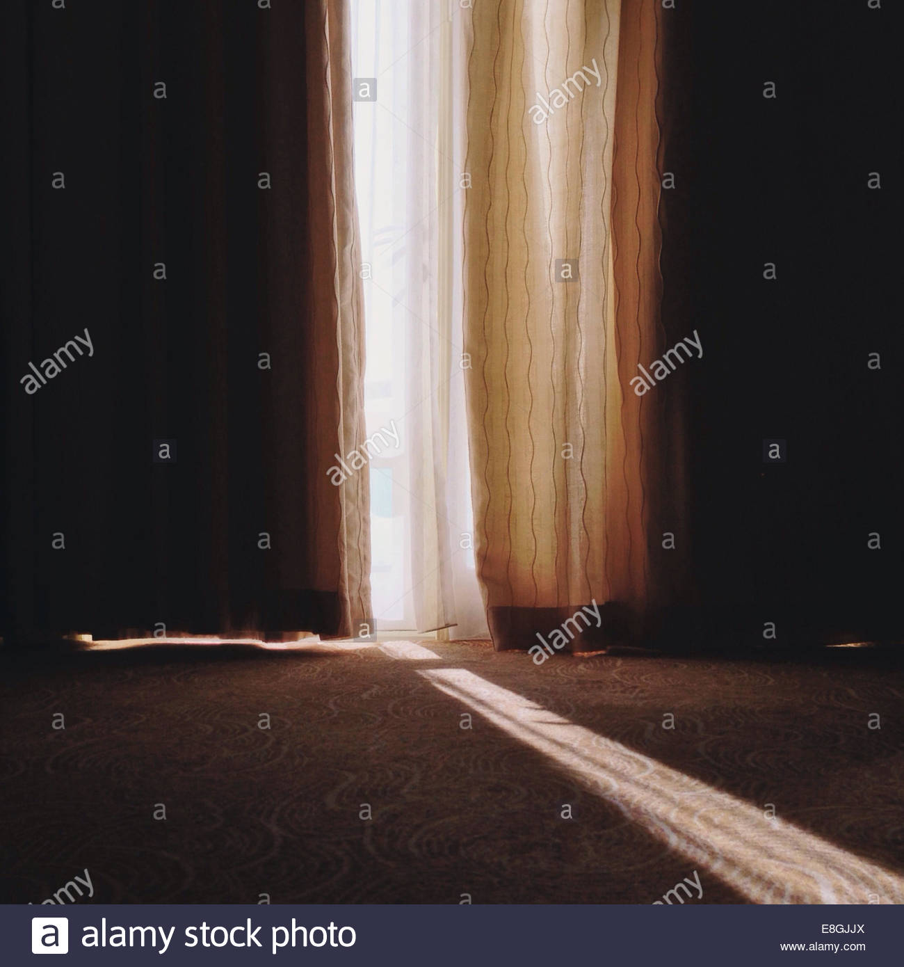 Sunbeam durchschimmern Lücke in Gardinen Stockbild