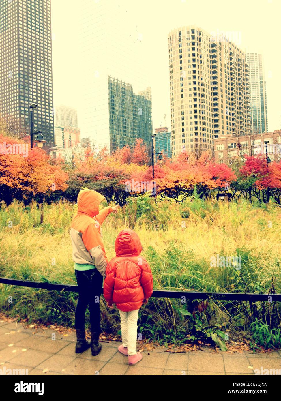Rückansicht der beiden Schwestern stehen im Park, Chicago, Illinois, Amerika, USA Stockbild