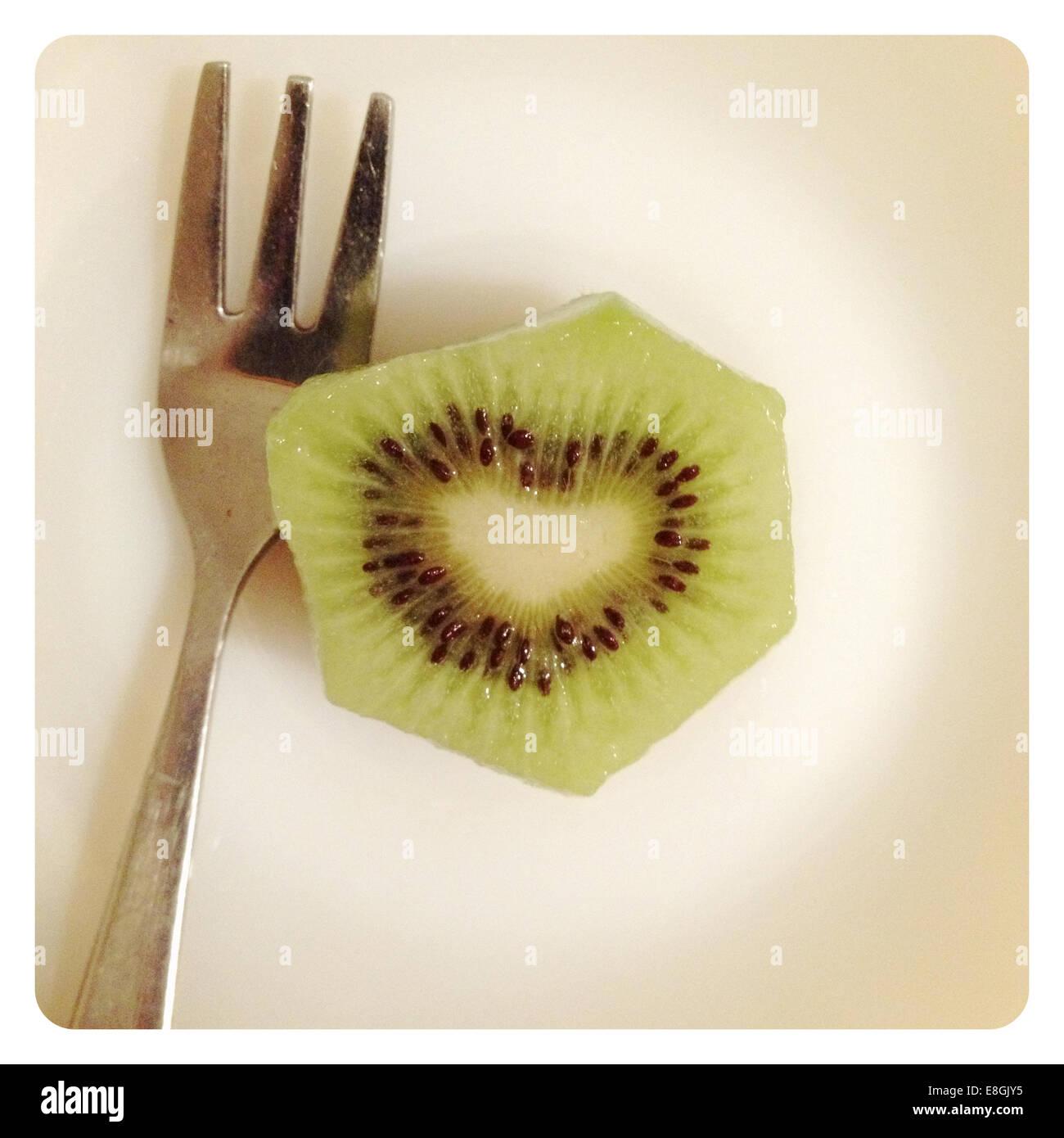 Kiwis mit Herz Form Samen und Gabel Stockbild
