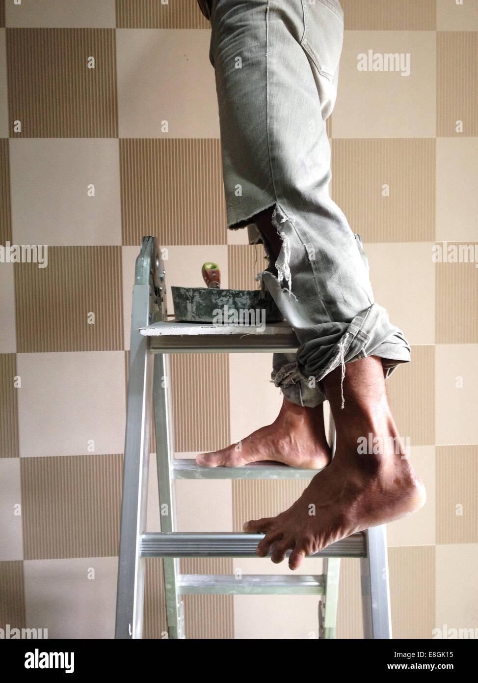 Spezielle Hauptstadtregion Jakarta, Indonesien, Jakarta, Mann stand auf Leiter Stockfoto