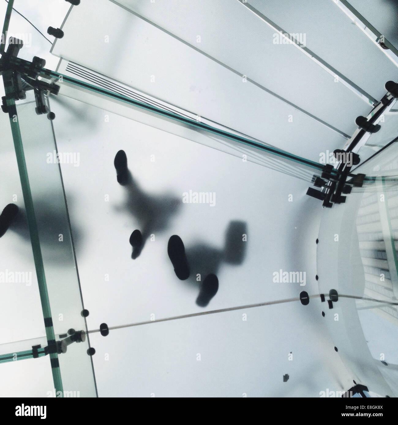 Niedrigen Winkel Blick der Passanten auf Glasboden Stockbild
