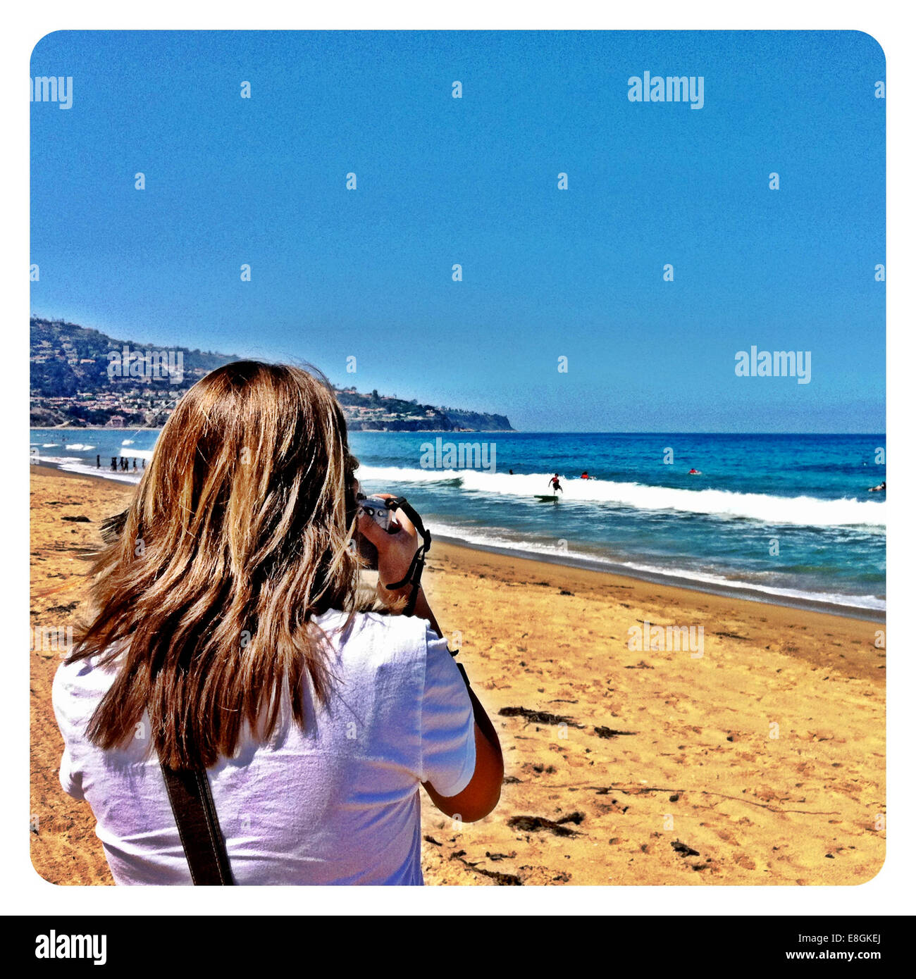 Hintere Ansicht o Frau nehmen Foto am Strand Stockbild