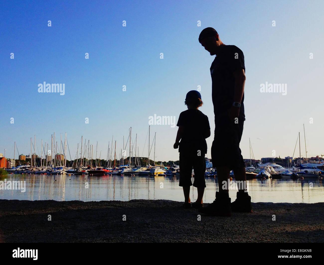 Stockholm, Schweden-ein Junge und sein Vater werfende Felsen ins Wasser und Blick auf Boote Stockbild