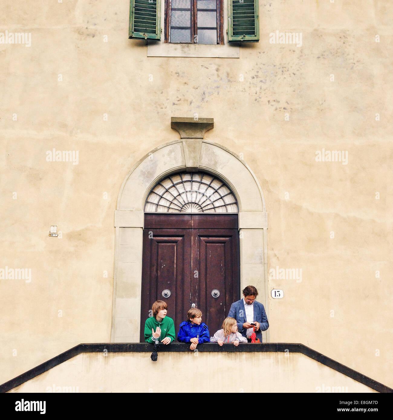 Italien, Florenz, Vater mit drei Kindern (10-11, 12-13) stand vor Gebäude Stockbild
