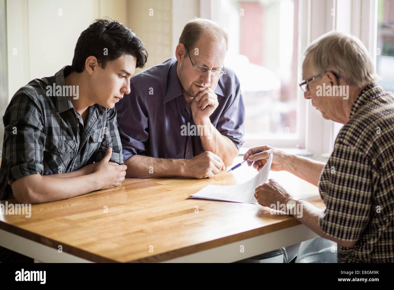 Familie diskutieren über Dokumente am Tisch Stockbild