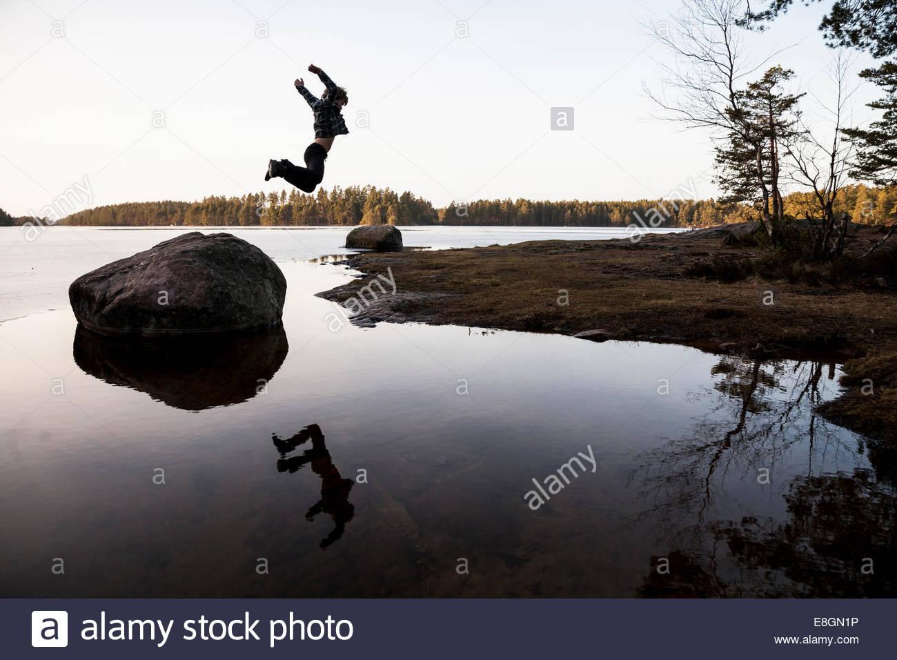 Voller Länge des jungen springen von Stein über dem Wasser Stockbild