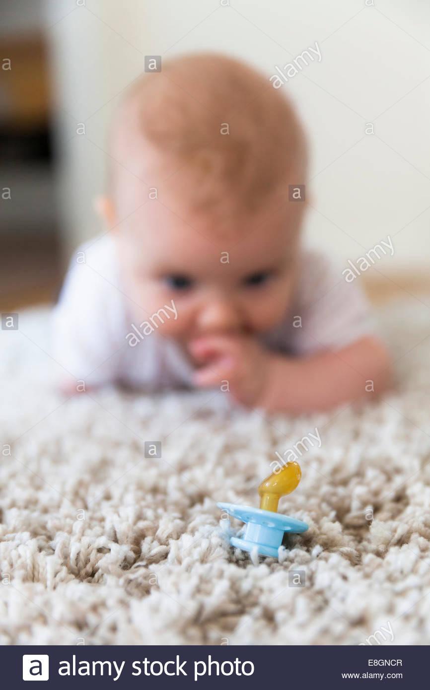 Babymädchen Blick auf Schnuller auf Teppich Stockbild