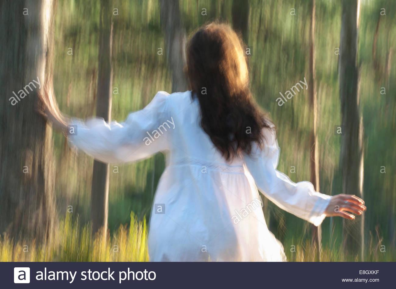 Rückansicht der Frau läuft im Wald Stockfoto