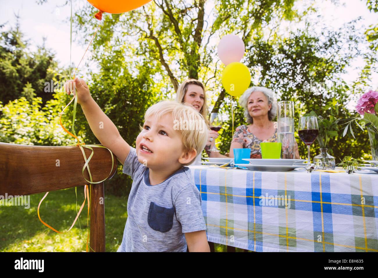 Junge am Tisch mit Familie aus drei Generationen im Garten Stockbild