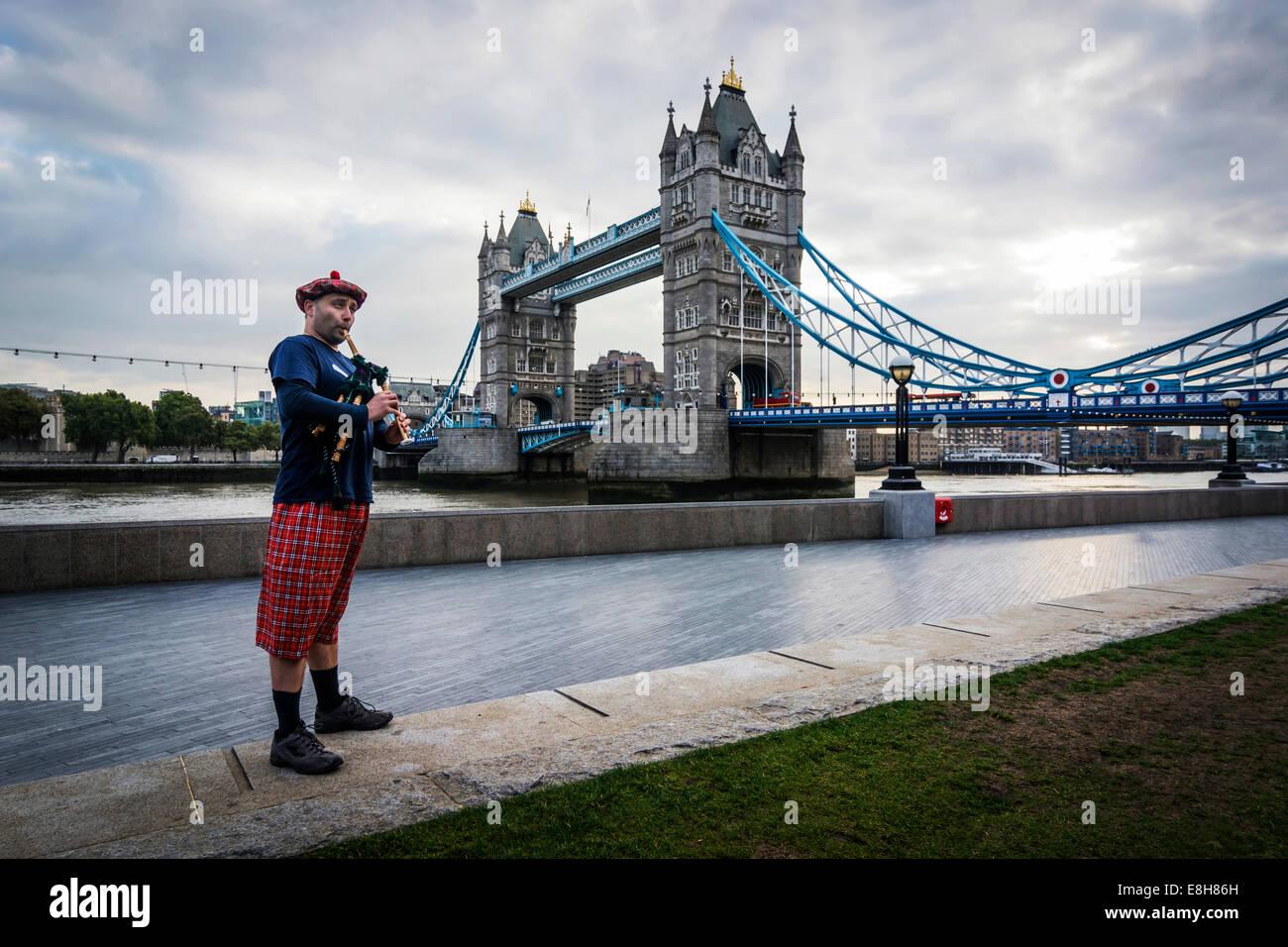 UK, London, schottischer Dudelsackspieler an der Tower Bridge Stockbild