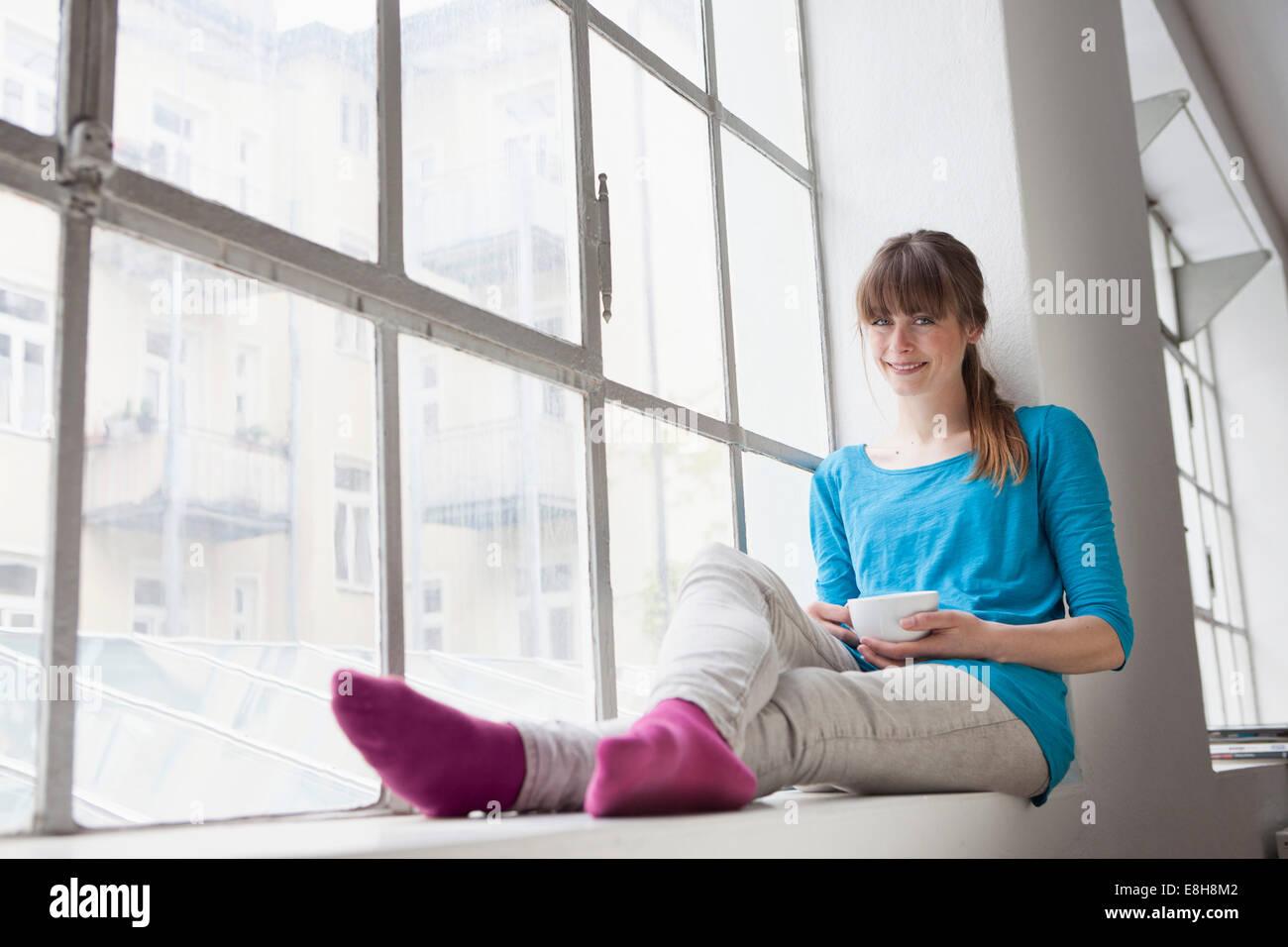 Porträt der lächelnde junge Frau mit Tasse Kaffee auf der Fensterbank in einem Büro sitzen Stockfoto